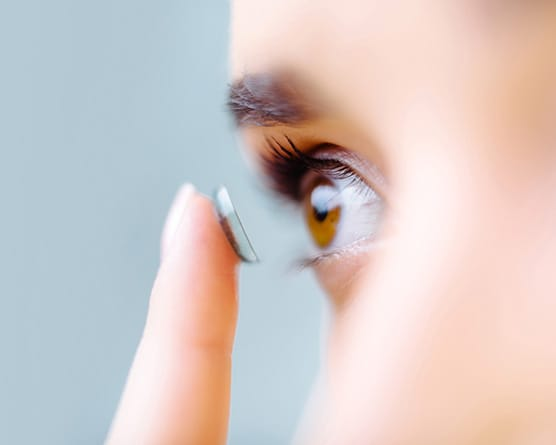 Woman putting contact lense in her eye